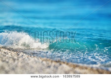Azure sea waves. Miniature tilt shift lens effect. Clear blue water with white foam. Pebbles on the beach. Nice France. Summer in Europe.
