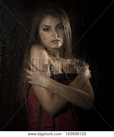 Portrait of a sensual young sexy woman wearing corset, touching her hair and posing behind transparent glass covered by water drops