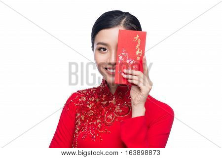 Portrait of a beautiful Asian woman on traditional festival costume Ao Dai holding red pocket - lucky money. Tet holiday. Lunar New Year. Text mean Lucky and Happy