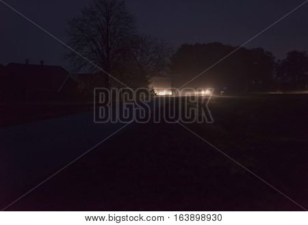 Car With Headlights Driving On Rural Road At Night.