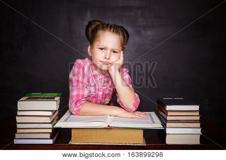 Schoolgirl sitting at a desk among stacks of books with her hands folded and her head resting on a large open book on a background of black slate. Free space. Black background. School concept