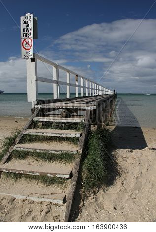 Stepping up to the jetty on the Sorrento beach, Victoria, Australia