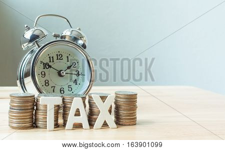 Concept tax time season and alarm clock with coins stack on wood table copy space