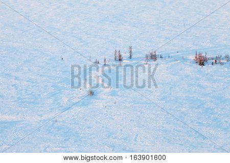 Aerial view above the snow covered tundra in time of short winter day.