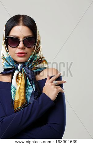 Girl in sunglasses and headscarf on head on gray background blank