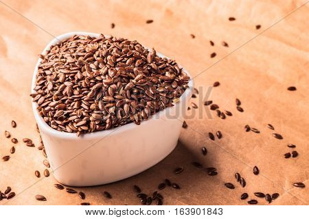 Healthy food diet. Brown flax seeds linseed in white bowl on paper background