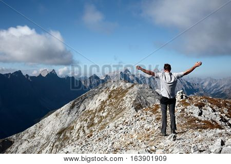 lucky man is standing on top of a mountain