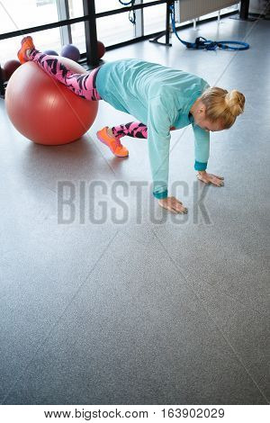 Photo of young athlete on fitball at gym