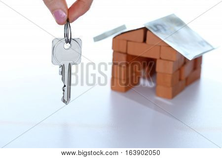 symbolic key with house model in background