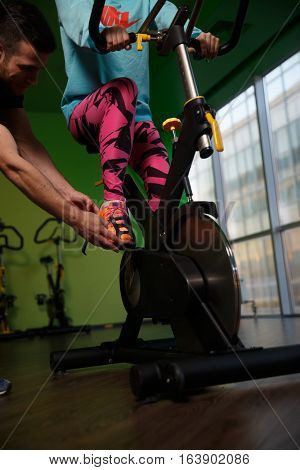 Coach helps women engaged on stationary bike in gym
