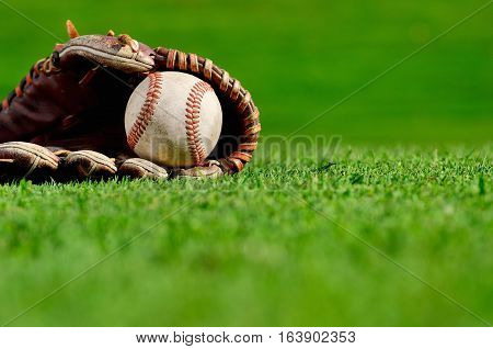 Baseball glove and baseball on the field