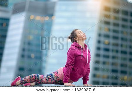 Young attractive model practicing yoga, stretching in upward facing dog exercise, Urdhva mukha shvanasana pose, working out wearing pink sportswear, outdoor full length, skyscraper background
