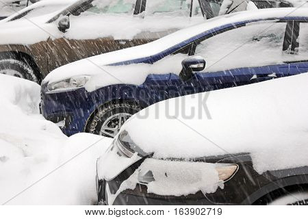 Details of three cars with doors headlights and rear view mirrors covered with thick layer snow during snowstorm. Shallow depth selective focus.