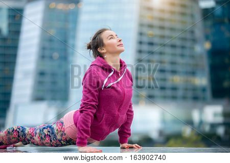 Young attractive woman practicing yoga, stretching in upward facing dog exercise, Urdhva mukha shvanasana pose, working out wearing pink sportswear, outdoor, modern skyscraper background