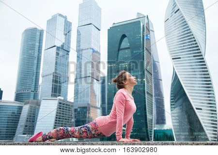 Young attractive woman practicing yoga, standing in upward facing dog exercise, Urdhva mukha shvanasana pose, working out wearing pink sportswear, outdoor full length, urban skyscraper background