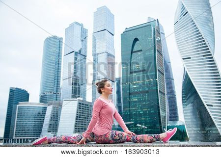 Young attractive woman practicing yoga, sitting in Monkey God exercise, Splits, Hanumanasana pose, working out wearing pink sportswear, outdoor full length, modern urban skyscraper background