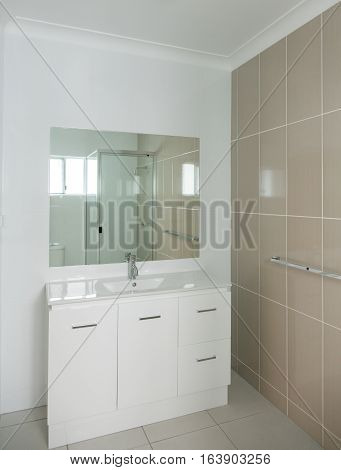 New compact ensuite bathroom with vanity and tiled walls