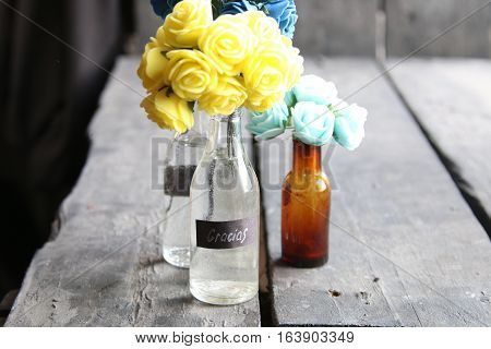 flowers in a bottle on old vintage table and tag Gracias