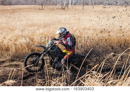KHABAROVSK RUSSIA - OCTOBER 23 2016: Enduro bike rider on a field with dry grass in autumn. The motorcycle skids and makes a lot of mud splashes