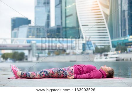 Young attractive woman practicing yoga, lying in Dead Body exercise, Savasana, Corpse pose, working out wearing pink sportswear, outdoor full length, modern skyscraper and river background