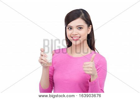 Happy young woman holding a glass with milk and showing thumbs up