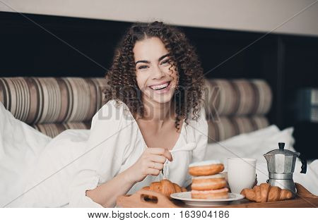 Laughing woman 20-24 year old having breakfast with donuts and coffee in hotel room. Looking at camera. Good morning.