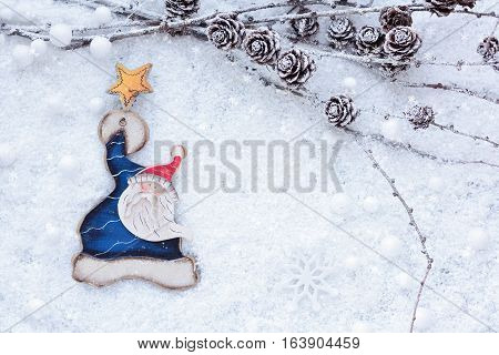 Larch Branches With Cones And Santa Claus On The Snow. Christmas Background With Space For Your Text