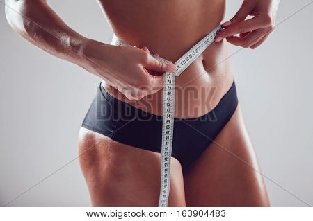 Athletic slim woman measuring her waist by measure tape on grey background