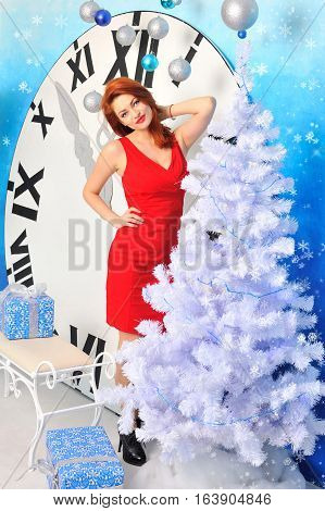 The Young Red-haired Woman In A Red Dress Near Christmas Tree