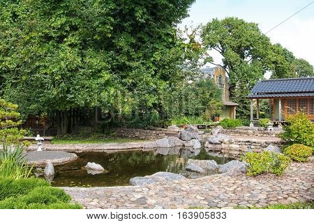 SAINT-PETERSBURG, RUSSIA, AUGUST 3, 2016: Fragment of The Japanese Garden with tea house and pond in Peter the Great Botanical Garden (Botanic Gardens of the Komarov Botanical Institute)