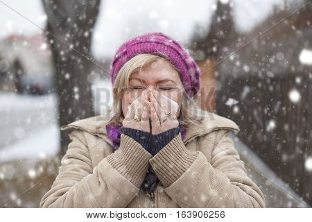 Woman sneezing outdoor in snowfall have influenza cold winter