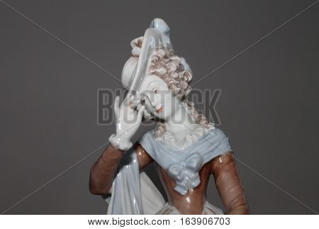 Porcelain figurine of a lady on a gray background