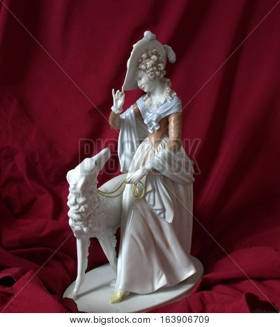 Porcelain figurine lady with dog Against the background of red velvet