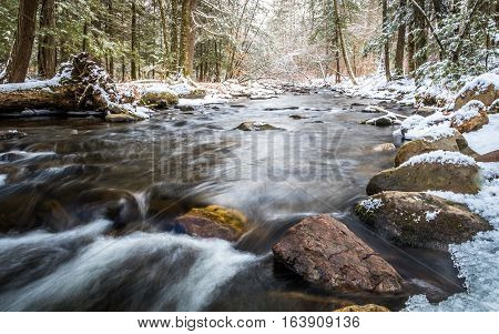 Winter river in the forest with river flowing gently along large rocks