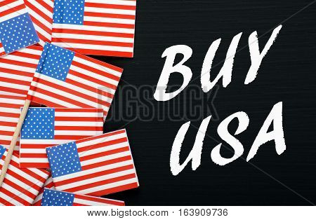 The words Buy USA in white text on a blackboard next to United States of America flags as a reminder to buy American products and services