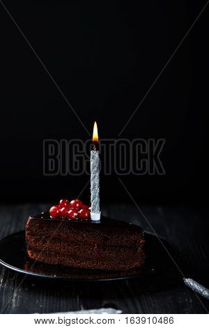 A slice of chocolate cake with redcurrant and a single lit candle on a dark background. Vertical shot. Dark shot. Low key.