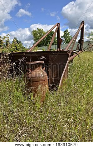 A rusty cream can is left in a weedy pasture by an old front end loader