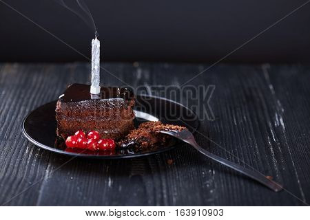 A slice of chocolate cake with redcurrant, fork and a single extinguished candle on a dark background.