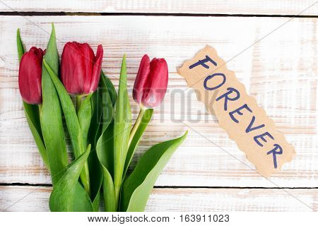 word FOREVER and bouquet of tulips on wooden background