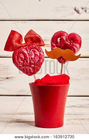 Candy with mustache in flowerpot. Heart-shaped sweets on white background. Romance is alive.