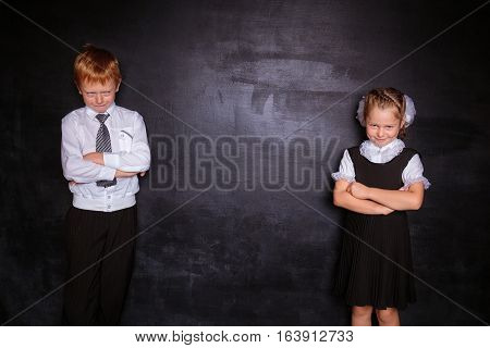 Schoolgirl and schoolboy stand near a school board frowning. Free space. Black background. School concept