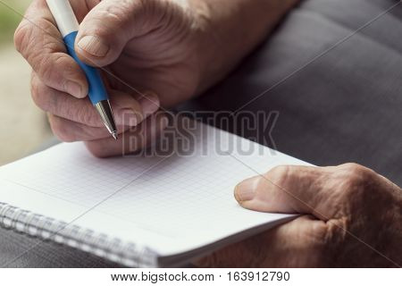 Detail of an elderly woman's hands holding a pen and writing a grocery list. Selective focus