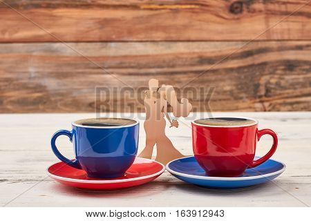 Wooden shape couple and cups. Mugs on saucers. Find a minute for coffee.