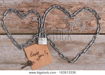 Love you card and chain. Keys near padlock. Relationship is strong as metal.
