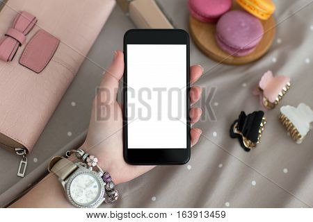 female hand with jewelry and watch holding a phone with isolated screen