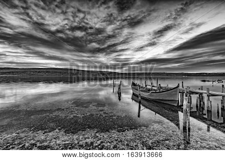 exciting black and white landscape on a lake with wooden pier and boat .
