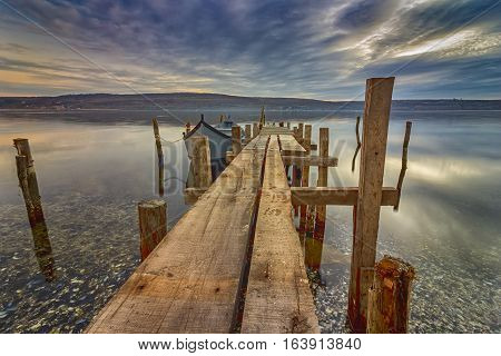 exciting long exposure landscape of wooden pier and boat in a lake.Close
