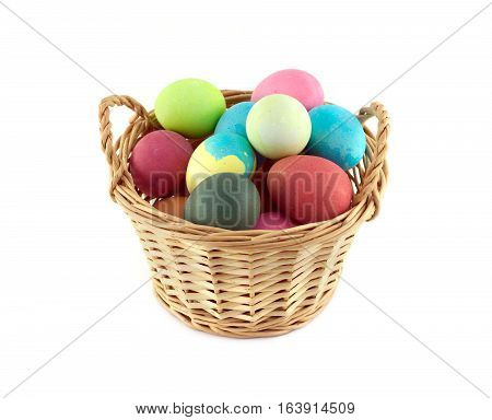 Colorful Easter eggs inside straw wicker brown basket isolated on white closeup
