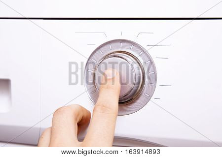 Men's hand presses a finger on the control button.