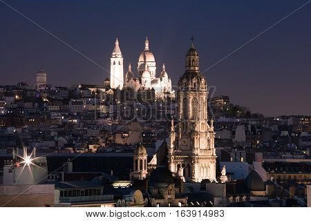 Aerial view of Sacre-Coeur Basilica or Basilica of the Sacred Heart of Jesus at the butte Montmartre and Saint Trinity church at night, Paris, France